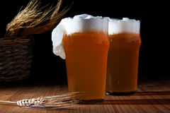 Glasses of beer. Two glasses of beer with grain on rough wooden table stock photos