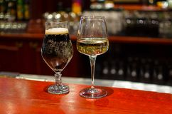 Glasses with beer and white wine. On a wooden table in cafe bar Royalty Free Stock Photo