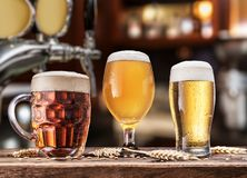 Glasses of beer on the wooden table. Blurred pub interior at the background royalty free stock photo