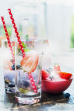Glasses  with berries lemonade with red straw and ice cubes on kitchen table over garden background. Royalty Free Stock Image
