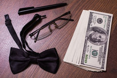 Glasses, black bowtie black pen, note book page and money Stock Images