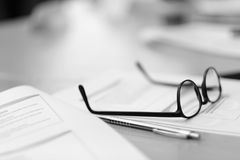Glasses with a black frame. Lie on the desk in the office Stock Photography