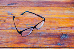 Glasses with black frame on wood. Glasses with black frame on wood table background royalty free stock photos