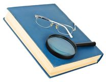 Glasses on a blue book Stock Images