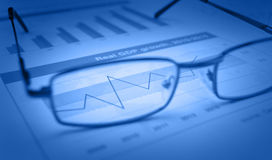 Glasses on blue financial chart and graph, success concept. Glasses on blue financial chart and graph, blue tone, success concept Stock Images