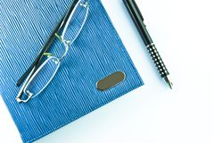 Glasses on blue notebook  with black pen Royalty Free Stock Photography