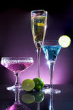 Glasses of blue, yellow and purple cocktail with green lime on t. He bar with dark tone pink background Stock Photography