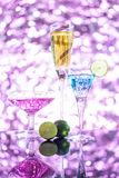 Glasses of blue, yellow and purple cocktail with green lime on t. He bar with sparkling pink background Royalty Free Stock Image