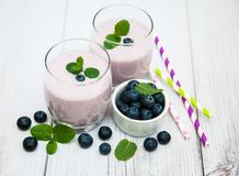 Glasses with blueberry yogurt on a table. Glasses with blueberry yogurt and fresh berries on a table stock photos