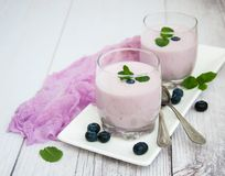 Glasses with blueberry yogurt on a table. Glasses with blueberry yogurt and fresh berries on a table stock image
