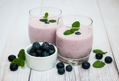Glasses with blueberry yogurt on a table. Glasses with blueberry yogurt and fresh berries on a table royalty free stock photography