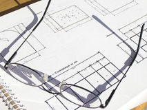 Glasses on a blueprint. Closeup with focus on glasses Stock Photos