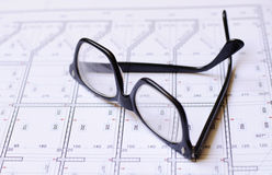 Glasses and blueprints Stock Photos