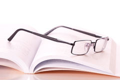 Glasses in a book. Isolated on white background Stock Photography