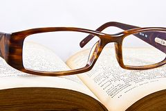 Glasses on a book Stock Images