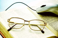 Glasses and book. Glasses and mouse on a book Stock Photo