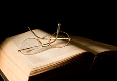 Glasses and Book. A pair of glasses lying on a book - text blurred slightly to avoid any copyright issues stock image