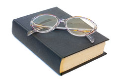Glasses on a book. Isolated on white Royalty Free Stock Image