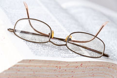 Glasses on the book. Glasses lying on open English dictionary closeup Stock Photo