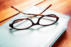 Glasses on a book. Leopard pattern reading glasses lying on a book. Shot on a wooden table stock image