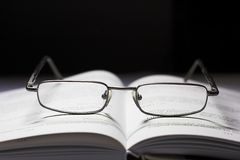 Glasses and a book. Centered symmetrical composition of glasses and a book Royalty Free Stock Image