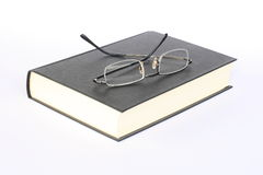 Glasses on book. A pair of reading glasses on a book stock photos