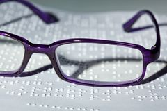 Glasses and book in Braille. Stock Images
