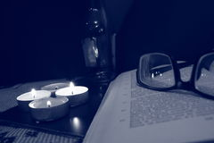 Glasses on the book and burning candles Royalty Free Stock Photography