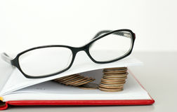 Glasses, book and coins Royalty Free Stock Images