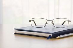 Glasses and a book on the desk Royalty Free Stock Photo