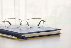 Glasses and a book on the desk Stock Photo