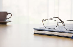 Glasses and a book on the desk Stock Image