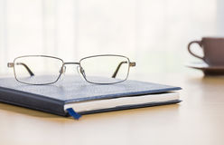 Glasses and a book on the desk Stock Images