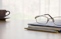 Glasses and book on the desk Royalty Free Stock Image