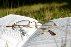 Glasses on a book with grass. Reading glasses on a book outside with grass Stock Photography