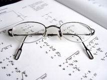 Glasses on Book II. Glasses on book with math formulas, closeup with focus on glasses stock image