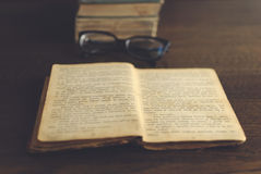 Glasses and book. Glasses and old book on table royalty free stock image