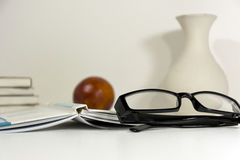 Glasses, book, orange, stack of books, a vase on a white table o Royalty Free Stock Images