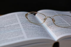 Glasses on book page. Close up of glasses on open book Stock Images