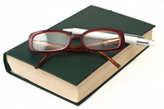 Glasses on book and pen Stock Photo