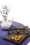 Glasses on the book and porcelain pitcher with lavender. Book and glasses on blue base anf small pitcher with flowers Stock Photos
