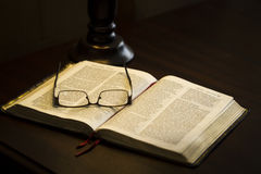 Glasses on book. A still life of reading glasses on an open book Stock Photography