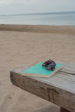 Glasses and book on wooden chair at Chao Lao Beach. Royalty Free Stock Photos