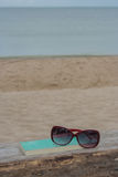 Glasses and book on wooden chair at Chao Lao Beach. Royalty Free Stock Image