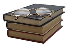Glasses on the books. Some books and a pair of glasses isolated on a white background royalty free stock photo