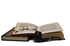 Glasses on the books and a pipe. Some books and a pair of glasses an a pipe isolated on a white background royalty free stock photo