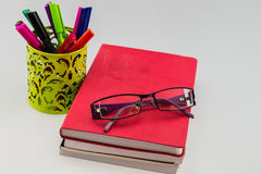 Glasses on books stack with basket of pen Royalty Free Stock Photography