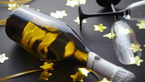 Glasses and bottle of champagne with golden serpentines and confetti stock video footage
