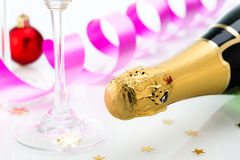 Glasses and bottle of champagne, serpentine isolated on a white background. Royalty Free Stock Images