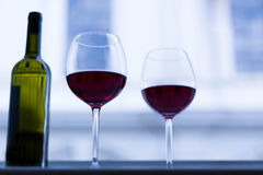 2 glasses and a bottle of red wine sitting on a open window in a European town. Close up of wine glasses of red wine Royalty Free Stock Image